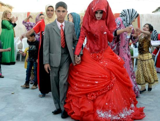 Hussein Younis Ali, 14 walks with his bride Nada Ali Hussein, 17, during the wedding party at his home in Tikrit, 150 km (93 miles) north of Baghdad, Iraq on October 8, 2013. Boys and girls are married at an early age in Iraq's rural areas by local clerics who ignore Iraq's law that forbids under-aged marriages under the age of 16. (REUTERS/Bakr al-Azzawi)