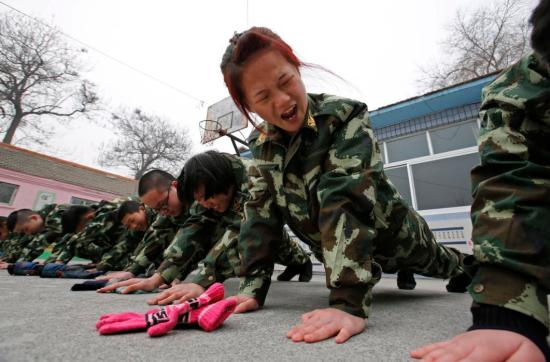 Students receive a group punishment during a military-style close-order drill class at the Qide Education Center in Beijing, China on February 19, 2014. The Qide Education Center is a military-style boot camp which offers treatment for internet addiction. As growing numbers of young people in China immerse themselves in the cyber world, spending hours playing games online, worried parents are increasingly turning to boot camps to crush addiction. Military-style boot camps, designed to wean young people off their addiction to the internet, number as many as 250 in China alone. (REUTERS/Kim Kyung-Hoon)