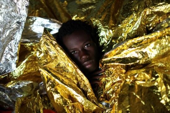 Mamahba, um rapaz guineense de 17 anos, coberto com um cobertor térmico depois de uma operação de salvamento no Mediterrâneo, perto da costa líbia, no início de Fevereiro Reuters/GIORGOS MOUTAFIS
